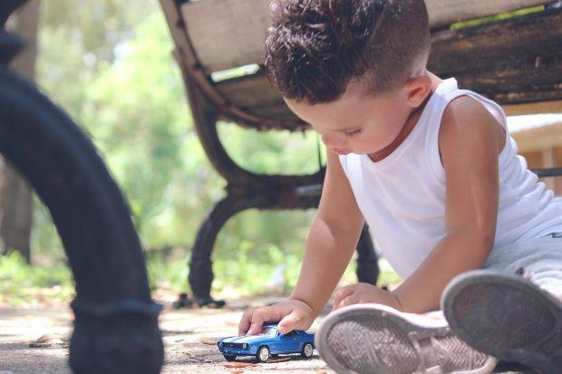 Малко момче, което си играе със синя количка