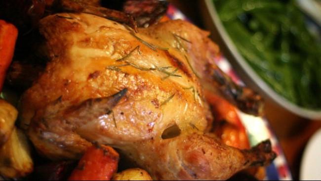 Печено пиле с розмарин върху подложка от зеленчуци