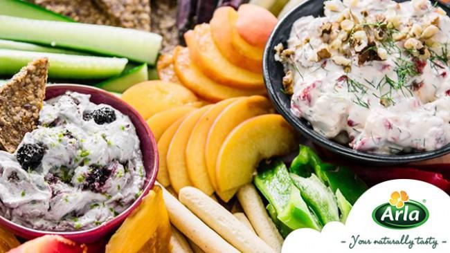 Цветна дъска с плодове, зеленчуци, крекери и два вида чийз дип